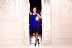 Viene La ragazza nelle porte bianche aperte del vestito blu ed entra in dell'interno dal buio Immagine Stock