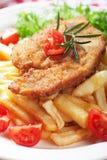Viener schnitzel, bröad biff med franska småfiskar Royaltyfri Foto