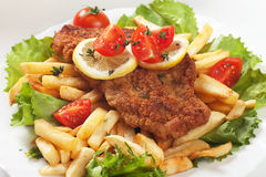Viener schnitzel, breaded steak with french fries. Lettuce and tomato Royalty Free Stock Image