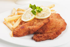 Viener schnitzel, breaded steak with french fries. Vienner schnitzel, breaded steak with french fries and lemon Stock Photography