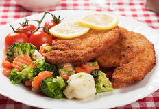 Viener schnitzel, breaded steak with healthy vegetables Royalty Free Stock Images