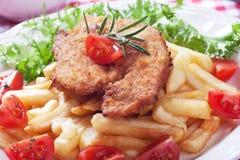 Vienerschnitzel, gepaneerd lapje vlees met frieten Stock Afbeelding
