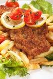 Vienerschnitzel, gepaneerd lapje vlees met frieten Royalty-vrije Stock Afbeeldingen