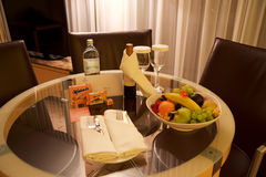 VIENNA, AUSTRIA - APR 28th, 2017: Romantic evening with bottle of red wine, sweets and fruits in the luxury hotel room. On a table with three leather chairs stock images