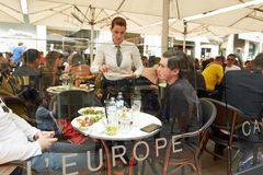 Vienna, Austria - 15 April 2018: A street cafe. Waiter and visitors at tables. Vienna, Austria - 15 April 2018: A street cafe. Waiter and visitors at tables Stock Photography
