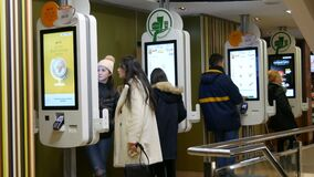 Vienna, Austria - December 19, 2019: Digital screen for orders without cashiers at McDonalds. People make fast food