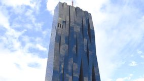 VIENNA, AUSTRIA - DECEMBER, 24 Hyperlapse of Donau City Tower reflecting clouds and blue sky. Modern office building in stock video footage