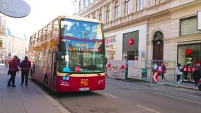 Tourist bus in old Vienna, Austria. VIENNA, AUSTRIA - FEBRUARY 17, 2019: The hop-on hop-off double-decker bus has arrived to the terminal station in city center stock footage