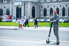 VIENNA, AUSTRIA - MAY 26: Modern city transport - People riding the streets on rented electric scooters by Lime S in Vienna,. Austria, on May 26, 2019 royalty free stock photos
