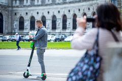 VIENNA, AUSTRIA - MAY 26: Modern city transport - People riding the streets on rented electric scooters by Lime S in Vienna,. Austria, on May 26, 2019 royalty free stock images