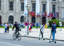 VIENNA, AUSTRIA - MAY 26: Modern city transport - People riding the streets on rented electric scooters by Lime S in Vienna,. Austria, on May 26, 2019 royalty free stock photography