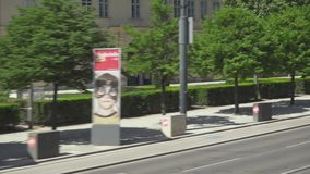 Traffic on the road by bus. VIENNA, AUSTRIA - MAY 2018 traffic on the road by bus along the sidewalk with young trees stock video footage