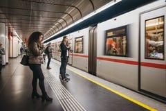 People standing on the underground platform in Vienna, Austria, train arriving, motion blur. Vienna, Austria - November 25, 2018: People standing on the stock images
