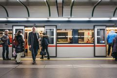 People on the underground platform in Vienna, Austria, train with open doors on the background. Vienna, Austria - November 25, 2018: People on the underground royalty free stock image