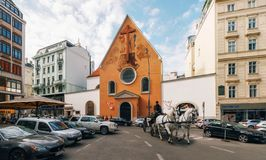 Capuchin Church which houses Imperial Crypt in Vienna. Vienna, Austria - 1 October, 2017: Horse-drawn carriage against Capuchin Church which houses Imperial royalty free stock images