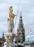 Vienna - Pallas Athene Statue. The Pallas Athene Statue in front of the Austrian Parliament Building (Hohes Haus), with the Town Hall (Rathaus) spire behind Stock Image
