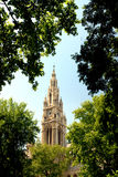Vienna -  Rathaus. The very prominent Rathaus spire (Town Hall) seen through the trees in front Royalty Free Stock Image
