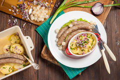 Vienna sausages with potato salad and pickled onions on a wooden table. Boiled sausages with potato salad, red and green onions on dark wooden background Royalty Free Stock Image