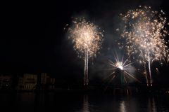 Vienne firework over the Rhône. Firework display over a Rhône's bridge in Vienne. Some houses on the left of the picture are illuminated by the firework royalty free stock photo