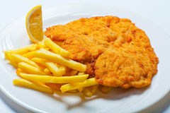 Viennese Schnitzel with fries on the white plate royalty free stock images