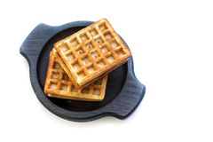 Viennese waffles on white. Photo of a pair of typical viennese waffles served on neat round dark plate made of dry oak wood. Viennese wafers usually are square stock photos