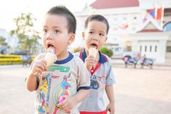 Laos twin boys enjoy eating ice cream cones in summer hot weather. Vacation time. Vientiane City. Laos. stock image