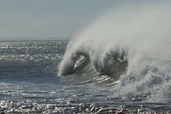 Viento tropical fuerte que crea el espray en una onda de fractura enorme imagenes de archivo