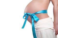 Vientre con el arqueamiento de la cinta azul de embarazado Foto de archivo