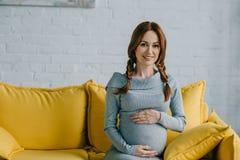 vientre conmovedor atractivo de la mujer embarazada y mirada de la cámara Imágenes de archivo libres de regalías