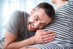 Vientre conmovedor del padre futuro feliz de la mujer embarazada Foto de archivo
