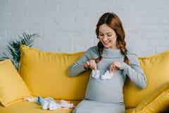 vientre conmovedor feliz de la mujer embarazada con los zapatos recién nacidos Imagenes de archivo
