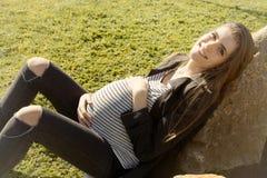 Vientre conmovedor joven hermoso de la mujer embarazada que se sienta en el parque que mira la cámara Fotografía de archivo libre de regalías