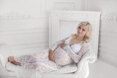 Vientre conmovedor sonriente feliz hermoso de la mujer embarazada que miente en m Imagen de archivo libre de regalías