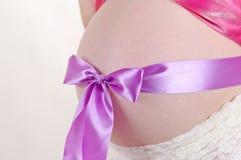 Vientre de la mujer embarazada atado con el arco púrpura Imagen de archivo libre de regalías