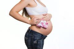 Vientre de la mujer embarazada con botines del bebé Imagen de archivo libre de regalías