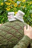Vientre de la mujer embarazada con botines del bebé Foto de archivo
