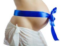Vientre de la mujer embarazada con la cinta azul Fotos de archivo