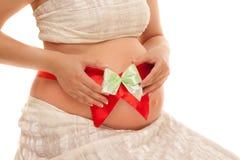 Vientre de la mujer embarazada con la cinta roja Fotografía de archivo libre de regalías