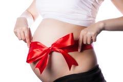 Vientre de la mujer embarazada con la cinta roja y el arco grande Imagen de archivo libre de regalías