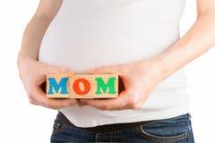 Vientre de la mujer embarazada con las manos que llevan a cabo bloques de madera coloridos con la muestra de la mamá Imagen de archivo libre de regalías