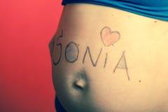 Vientre de la mujer embarazada con los dibujos foto de archivo libre de regalías