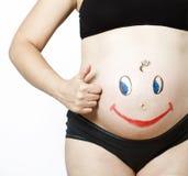 Vientre de la mujer embarazada en el fondo blanco Imágenes de archivo libres de regalías