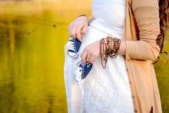 Vientre de la mujer embarazada que lleva a cabo botines del bebé Embarazo sano Fotografía de archivo