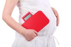Vientre de la mujer embarazada que lleva a cabo el equilibrio rojo Foto de archivo libre de regalías