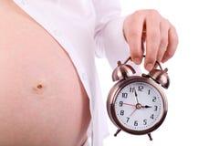 Vientre de la mujer embarazada que sostiene el reloj de alarma Imagen de archivo