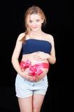 Vientre de la mujer embarazada s con la cinta y el arco rosados Fotos de archivo