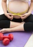 Vientre de medición de la mujer embarazada con la cinta después de ejercitar en ajuste Fotos de archivo libres de regalías