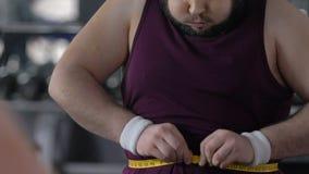 Vientre de medición del hombre gordo feliz con la cinta en el gimnasio, logro de la pérdida de peso, resultado almacen de metraje de vídeo