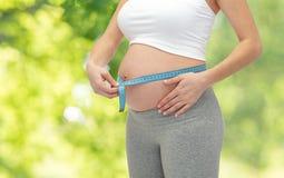 Vientre de medición de la mujer embarazada por cinta métrica Imagen de archivo