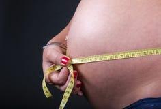 Vientre de mujeres embarazadas con medida Fotografía de archivo